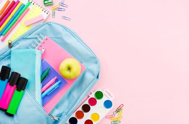 Vista superior de los elementos esenciales de regreso a la escuela con manzana y mochila