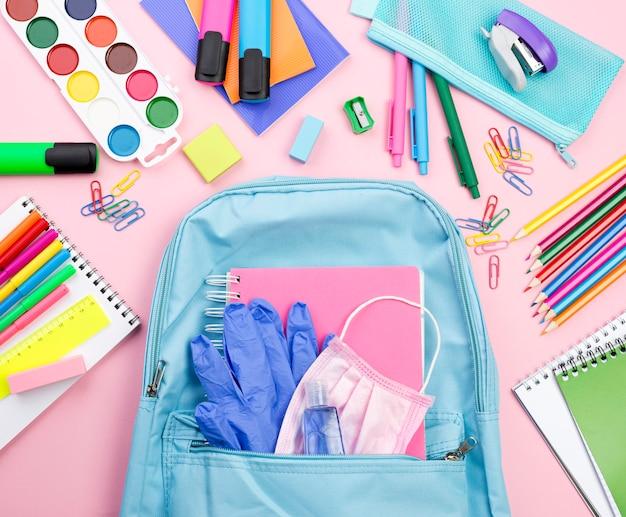 Vista superior de los elementos esenciales de regreso a la escuela con mochila y acuarela