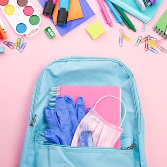 Vista superior de los elementos esenciales de regreso a la escuela con mochila y guantes.