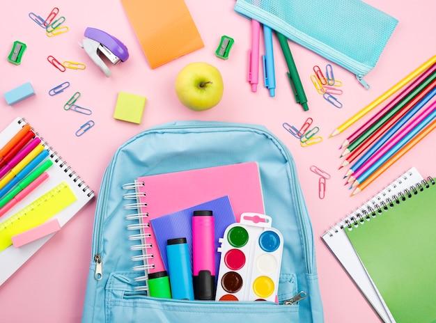 Vista superior de los elementos esenciales para el regreso a la escuela con mochila y lápices.