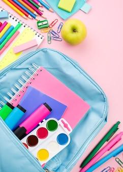 Vista superior de los elementos esenciales de regreso a la escuela con mochila y manzana