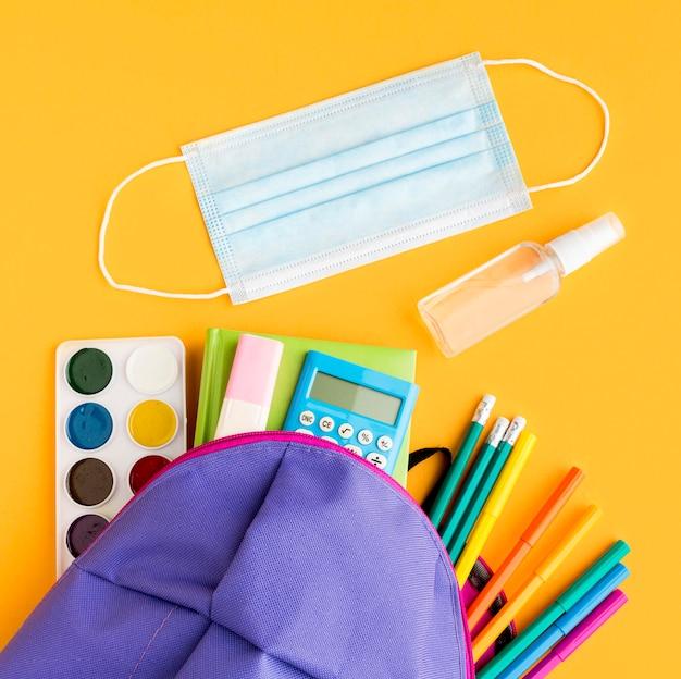 Vista superior de los elementos esenciales para el regreso a la escuela con mochila y máscara médica.