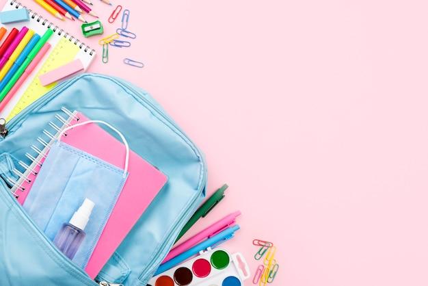 Vista superior de los elementos esenciales de regreso a la escuela con mochila