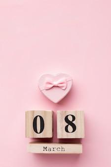 Vista superior de elementos femeninos de color rosa con letras de 8 de marzo