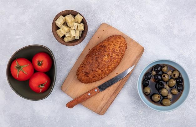 Vista superior de empanada en una tabla de cocina de madera con cuchillo con queso tomates y aceitunas sobre un fondo blanco.