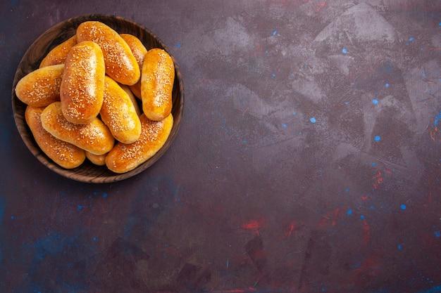 Vista superior empanadas dulces deliciosa masa horneada para té en el escritorio oscuro comida masa de repostería té comida empanada