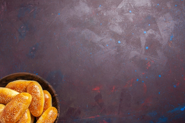 Vista superior empanadas dulces deliciosa masa horneada para té sobre fondo oscuro comida masa de pastelería comida empanada