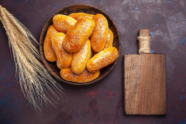 Vista superior empanadas dulces deliciosas tartas horneadas para té sobre fondo morado oscuro comida de té pastelería comida de masa de empanada