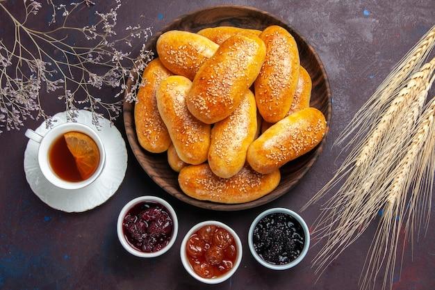 Vista superior de empanadas dulces con té y mermelada sobre fondo oscuro, comida de té, pastelería, masa de empanada, comida