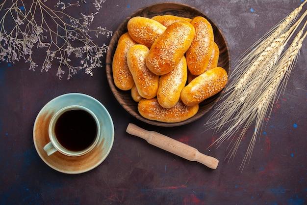 Vista superior empanadas dulces con té sobre fondo oscuro comida de té pastelería masa de empanada alimentos