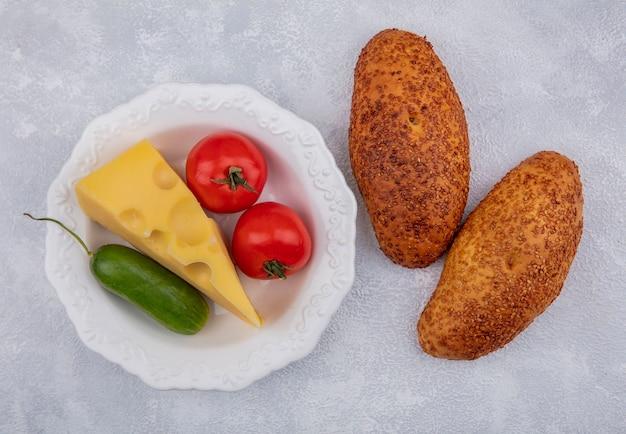 Vista superior de empanadas de sésamo fresco con tomate y pepino en un recipiente blanco sobre un fondo blanco.