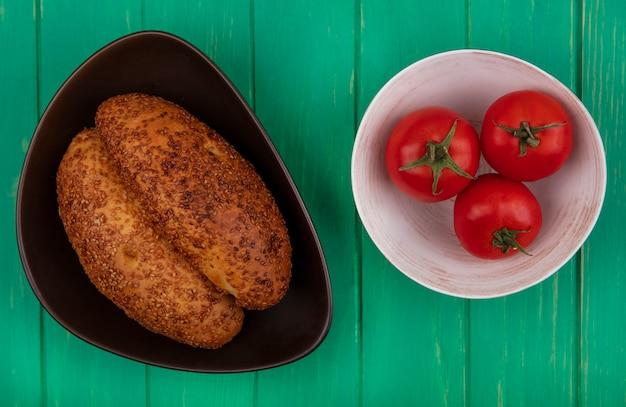 Vista superior de empanadas de sésamo suaves y deliciosas en un recipiente marrón con tomates frescos en un recipiente sobre un fondo de madera verde