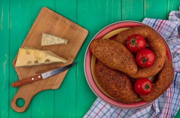 Vista superior de empanadas suaves y de sésamo en un recipiente con tomates frescos sobre un paño con queso sobre una tabla de cocina de madera con cuchillo sobre un fondo de madera verde