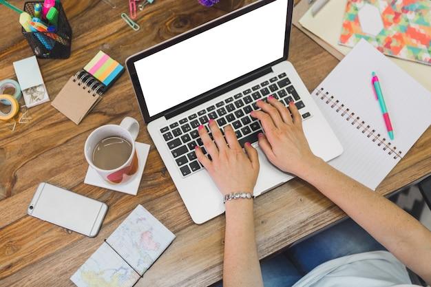 Vista superior de empleada trabajando con su portátil