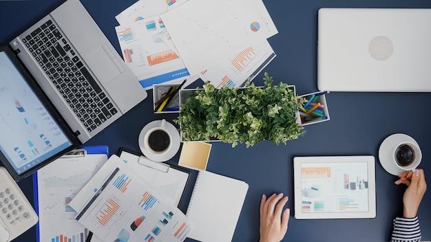 Vista superior de la empresaria analizando estadísticas de gráficos financieros tomando café