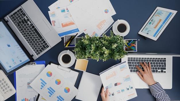 Vista superior de la empresaria escribiendo experiencia en contabilidad financiera en la computadora portátil