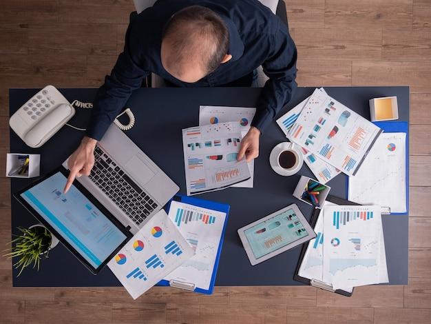 Vista superior del empresario apuntando a estadísticas financieras