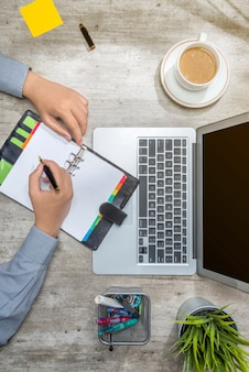 Vista superior del empresario escribiendo en cuaderno con laptop, café, notas adhesivas, planta en maceta y accesorios de negocios