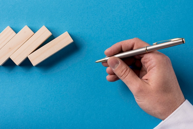 Vista superior del empresario con pluma con piezas de dominó