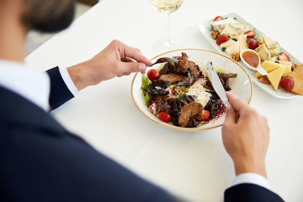 Vista superior de un empresario que está comiendo una ensalada de carne en el almuerzo de negocios