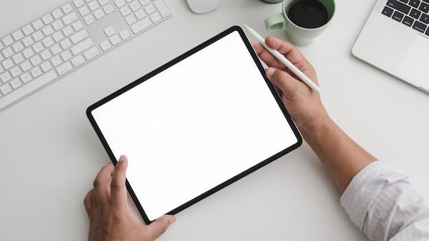 Vista superior del empresario trabajando en tableta en el práctico espacio de trabajo con computadora y laptop