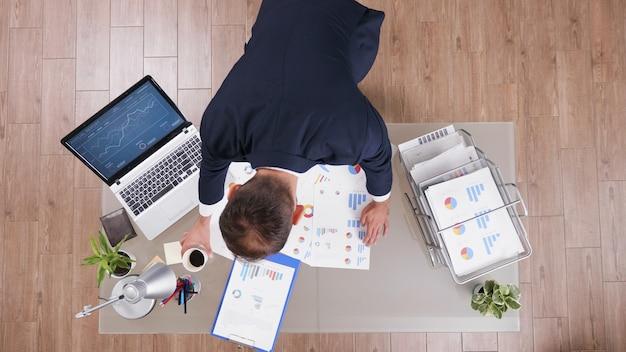 Vista superior del empresario en traje tomando café mientras analiza estadísticas de gestión