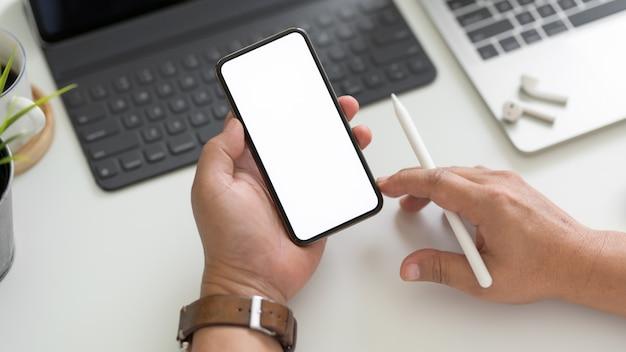 Vista superior del empresario usando el teléfono en el moderno espacio de trabajo con computadora portátil, tableta y otros suministros de oficina
