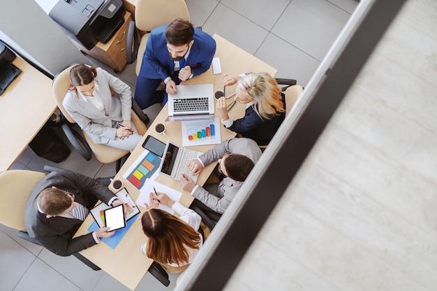 Vista superior de empresarios caucásicos en ropa formal sentados en la sala de juntas en el escritorio y analizar datos. en el escritorio hay computadoras portátiles, gráficos, tabletas y papeleo.