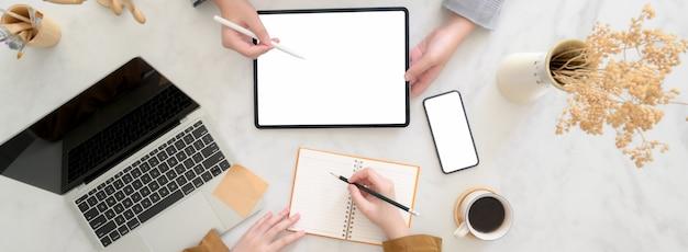 Vista superior de empresarios haciendo una lluvia de ideas sobre su proyecto con dispositivos digitales