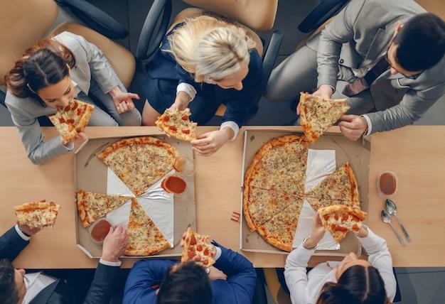 Vista superior de empresarios en ropa formal sentado a la mesa y comer pizza para el almuerzo.
