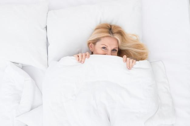 Vista superior encantadora mujer senior en la cama