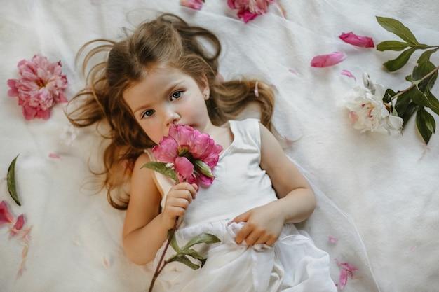 Vista superior de la encantadora niña pequeña que crece con una peonía rosa tenue acostada en una sábana blanca, rodeada de flores frescas, mirando seriamente
