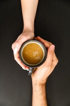 Vista superior de la encantadora pareja de enamorados cogidos de la mano con una taza de café caliente o té masala en mesa negra