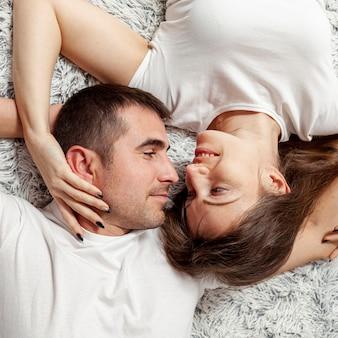 Vista superior encantadora pareja de jóvenes que buscan el uno al otro