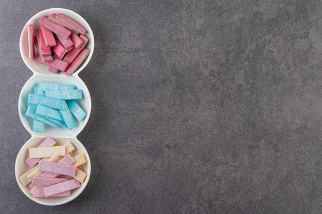 Vista superior de las encías en tiras de colores en la placa sobre la superficie gris