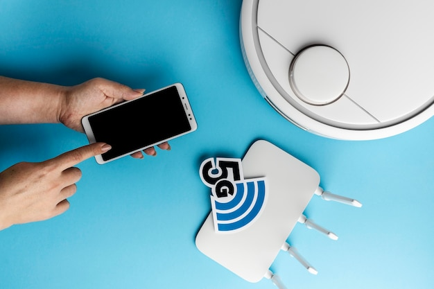 Vista superior del enrutador wi-fi con teléfono inteligente y aspiradora