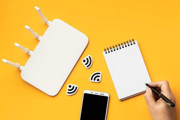 Vista superior del enrutador wi-fi con teléfono inteligente y computadora portátil