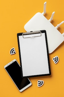 Vista superior del enrutador wi-fi con teléfono inteligente y portapapeles
