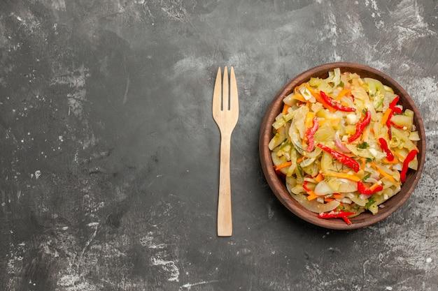 Vista superior de la ensalada una apetitosa ensalada de verduras en el cuenco de madera tenedor
