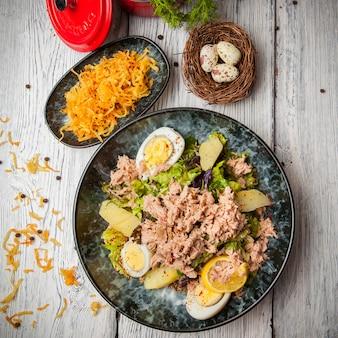 Vista superior ensalada de atún en un plato con huevos, papas y huevos en la mesa de madera