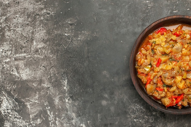 Vista superior de la ensalada de berenjena asada en un recipiente sobre una superficie oscura