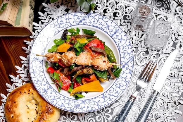 Vista superior de ensalada de carne con pimientos perejil cubierto con trozos de pollo en brochetas