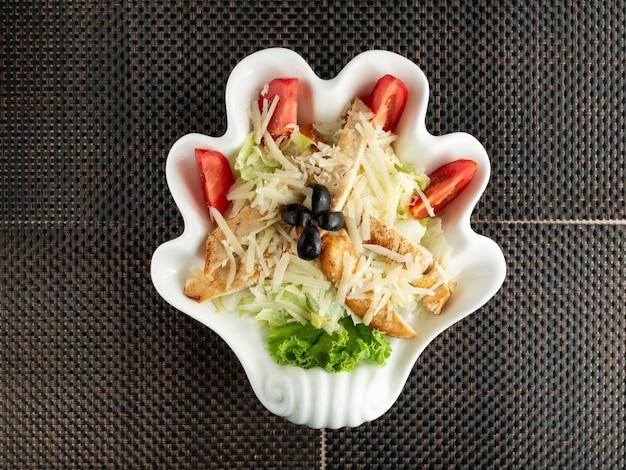 Vista superior de ensalada césar en plato en forma de mano
