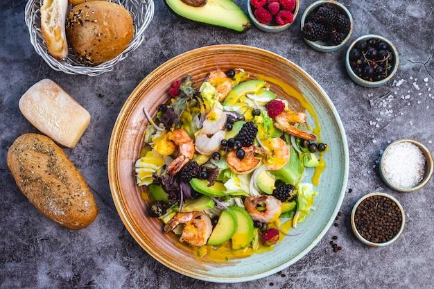 Vista superior de ensalada de dieta saludable con camarones fritos, aguacate, lechuga, cebolla roja y bayas