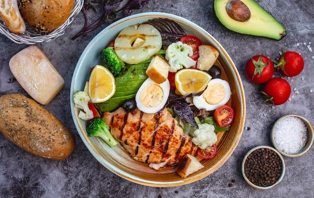 Vista superior de ensalada de dieta saludable con pollo a la parrilla, brócoli, coliflor, tomate, lechuga, aguacate y lechuga