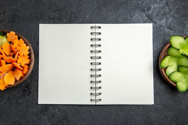 Vista superior ensalada diseñada en rodajas con bloc de notas sobre fondo gris ensalada de alimentos saludables dieta vegetal