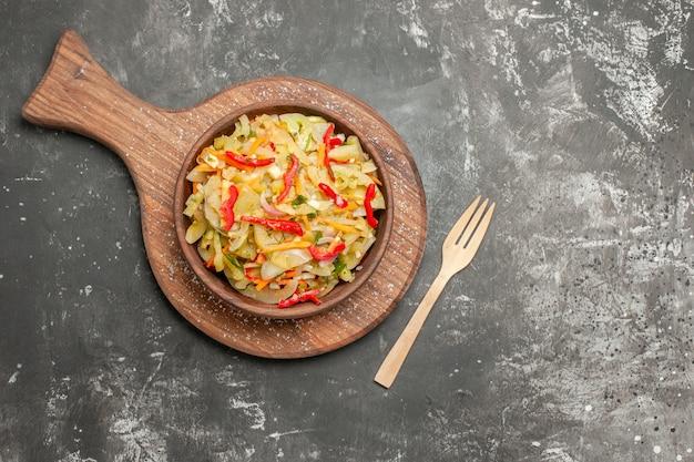 Vista superior de la ensalada ensalada de verduras en la tabla de cortar junto a la horquilla