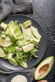 Vista superior ensalada fresca con aguacate sobre la mesa