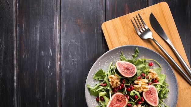 Vista superior de la ensalada de higos de otoño en un plato con cubiertos y espacio de copia