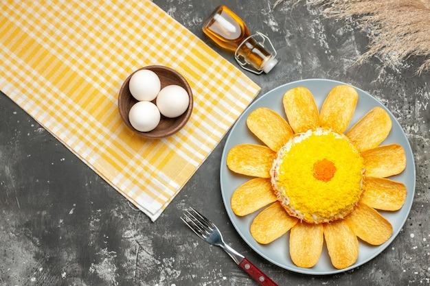 Vista superior de la ensalada en el lado derecho con servilleta amarilla botella de aceite tenedor trigo y tazón de huevos en el lado de la mesa gris oscuro